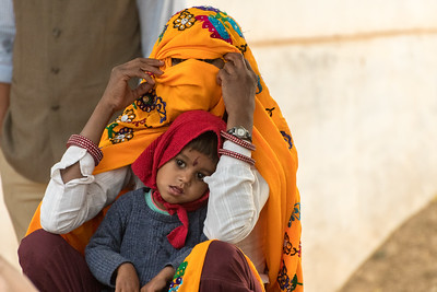 A village woman and child watch the dance demonstration.