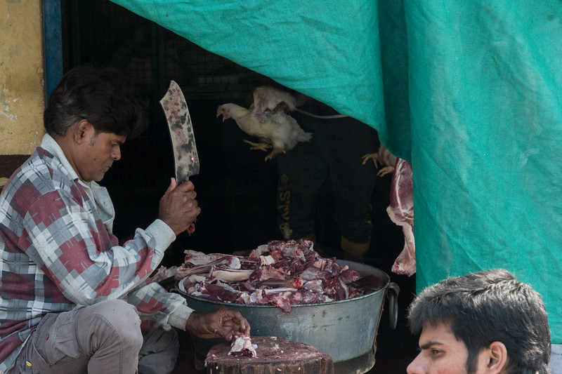A Varanasi street vendor butchers a goat on the sidewalk while his assistant weighs live chickens in a scale behind him.