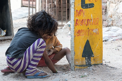 Two small children play along a back street in Jaipur.