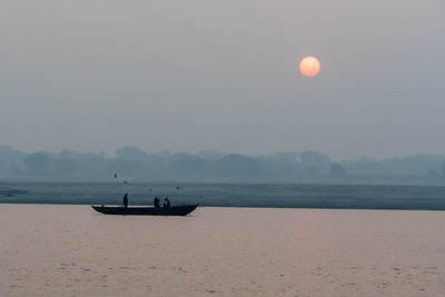 A man rows his boat along the Ganges River at sunrise.