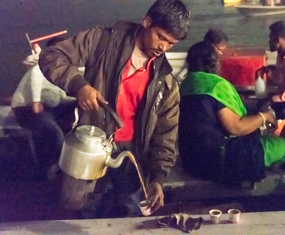 During the Aarthi ceremony in Varanasi, a chai wallah walks from boat to boat selling chai - with an ingeneous bucket of embers strapped to the bottom of his teapot.