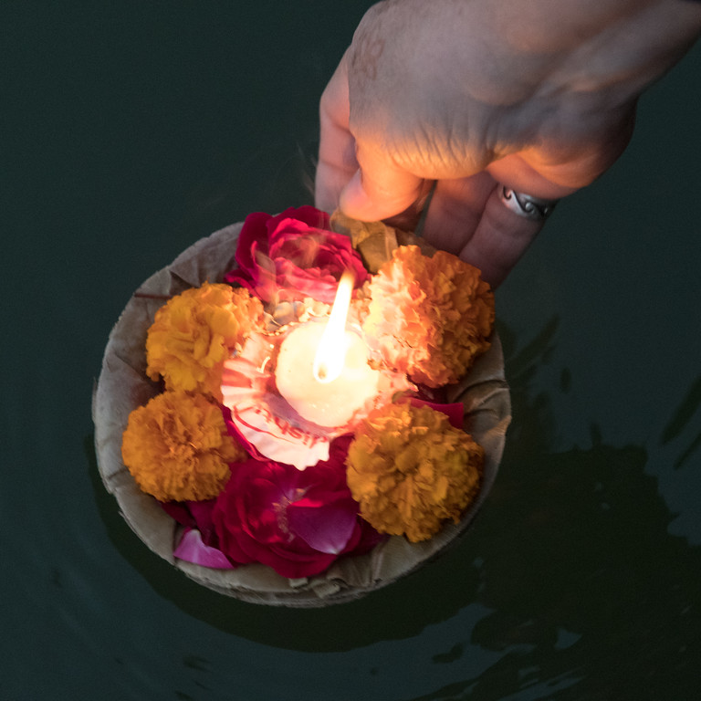 An offering of candle and flowers float on the Ganges River, Thanksgiving morning.