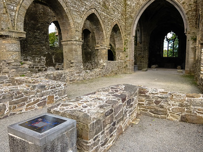 Main area of Jerpoint Abbey, with stainless steel plaque explaning the various phases of build and occupation at the site.