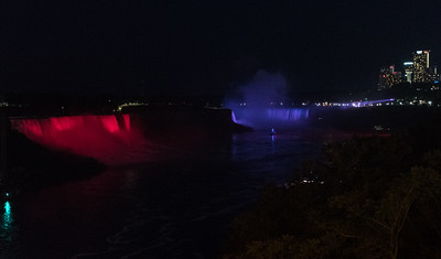 Niagara Falls from Rainbow Bridge across the Niagara River, at night when they illuminate the falls.