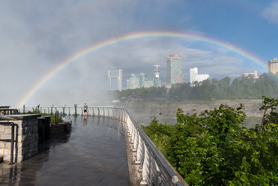 A rainbow frames a selfie-snapping tourist at Niagara's Horseshoe Falls in early morning.