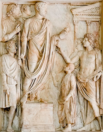 In the hallway by the entrance of the Hall of the Horatii and Curatii in the Capitoline Museums,  this bas-relief was originally on a monument honoring the Emperor Hadrian.  It shows him distributing food to needy children in a ceremony in which his deceased wife Sabina was diefied.
