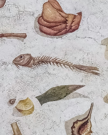Part of a mosaic showing messy dining room (triclinium) from Rome probably from the time of Hadrian who ruled from 117 o 138 BC.  The theatrical mask in this gallery was at the triclinium entrance.<br /> <br /> Vatican Museums, Rome