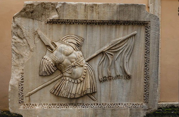 In the courtyard of the Capitoline Museums were several bas-reliefs with a warrior's torso, a lance struck through the body and a flag perpendicular to the lance. <br /> <br /> I have no idea what the purpose of these pieces is.