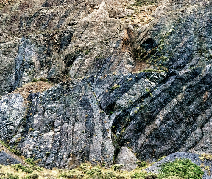 "2018-03-24 Stone formation showing the uplift of various layers from horizontal to as much as a 90 degree angle.  Taken near Red Rocks Walkway in the vicinity of Te Kopahou Visitor Center and about 9 km SW of Wellington, New Zealand. Coords: 41°20'47"" S 174°44'44"" E"