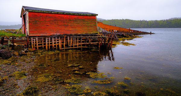 Decaying boathouse near decaying boat.