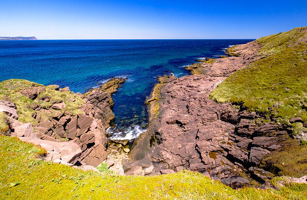 Ruged pink rock of the Cape Spear coastine.