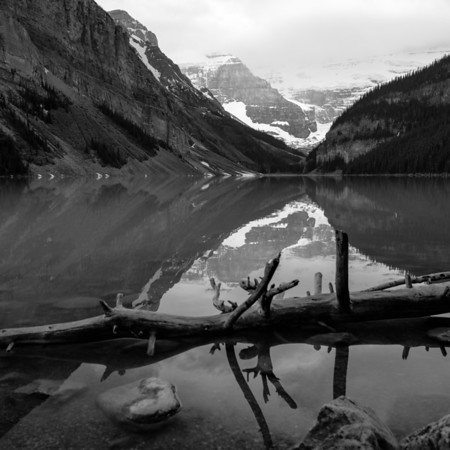 More calm Lake Louise reflects as the trail winds around the lake.