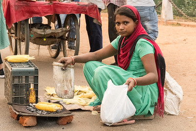 A street vendor prepares to sell roasted corn, on Rajpath in Delhi.