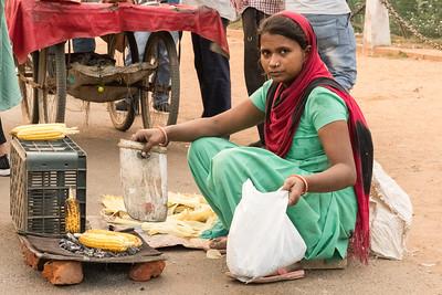 A street vendor prepares to sell roasted corn, on Rajpath in Delhi.