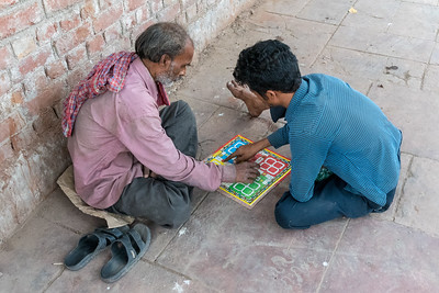 Two men play a board game on the sidewalk in Old Delhi.