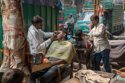 A sidewalk barbershop in Old Delhi.