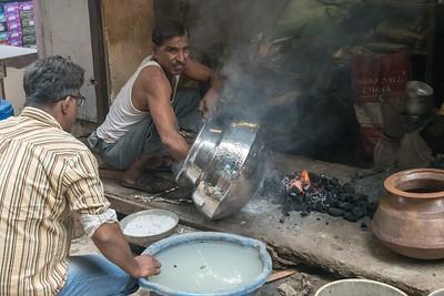 Polishing a silver pot at a roadside shop, Old Delhi.