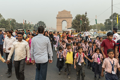 People cross the street, near the India Gate in Delhi.