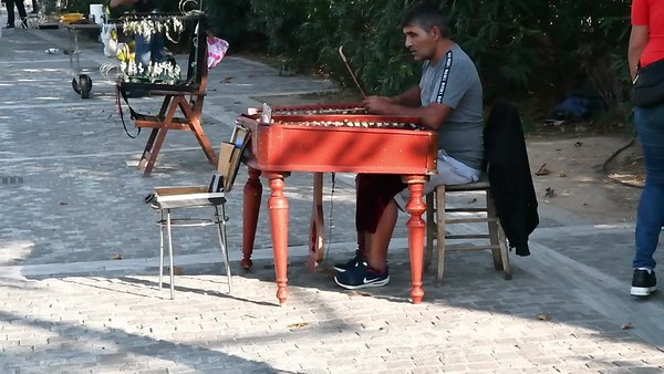 A street musician plays an instrument somewhat like a hammered dulcimer; Athens.