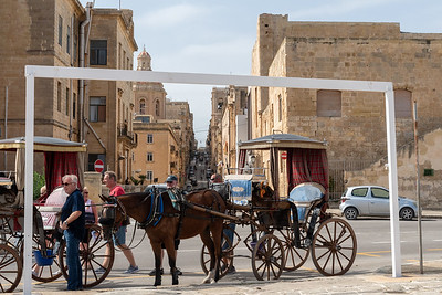 Horse carriages offer rides through the streets, in Valleta, Malta.