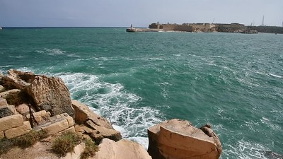 Waves splash the rocky shores of the harbor in Valleta, Malta.