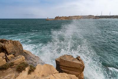 Waves splash the rocky shores of the harbor in Valleta, Malta.