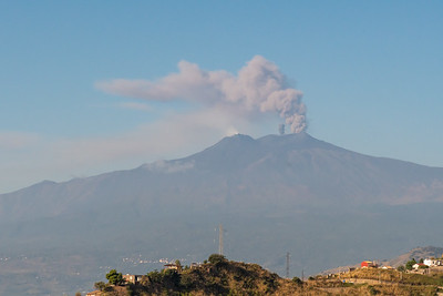 Mount Etna puffs with a fresh explosion, viewed from Taormina, Sicily.