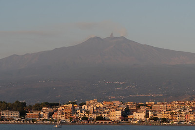 Mount Etna erupts at sunrise, from offshore of Naxos, Sicily.