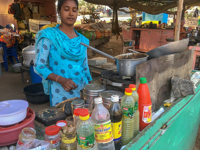 A vendor prepares chai with cardamon and ginger, Hampi.