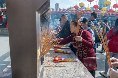 Pilgrims place incense in front of Wang Tai Sin temple in Hong Kong.