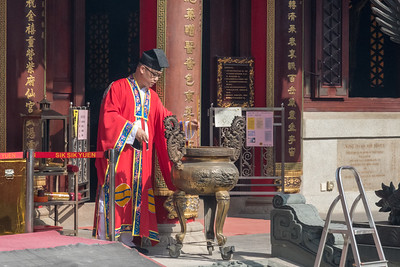 The monk(?) of the temple emerges to set incense into an urn at the entrance to Wang Tai Sin temple in Hong Kong.