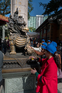 Pilgrims seek good luck by rubbing the bronze dragon at the entrance to Wang Tai Sin temple in Hong Kong.