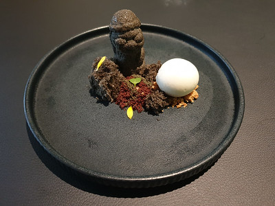 """Dessert at Jungstix Café in Seoul; the statue is ice cream molded to look like ancient statues from Jeju island, and the """"volcanic rocks"""" are crumbled chocolate cake."""