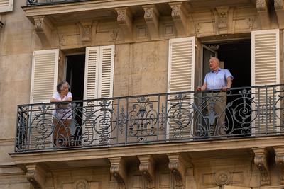 Neighbors watch the Paris Triathalon from their veranda.