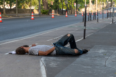 A sleeping drunk on a Paris sidewalk, ignored by passersby.