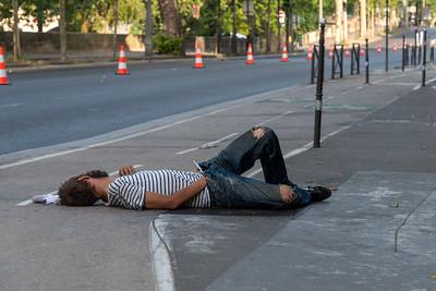 A sleeping drunk on a Paris sidewalk, ignored by passersby.