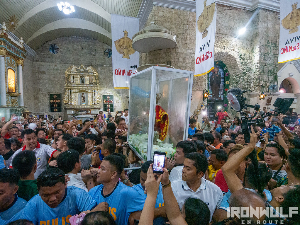 Devotees bringing the Sto Niño back in it's pedestal