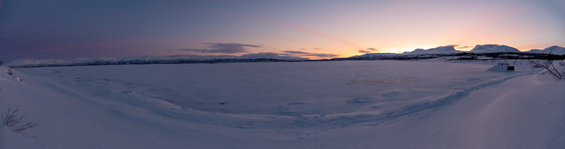 """Panoramic view from the shore of Lake Torneträsk, before sunrise. Lapporten (""""The Lapponian Gate"""") at right."""