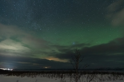 Northern Lights as seen from Abisko. At lower-left, the lights of Björkliden village.