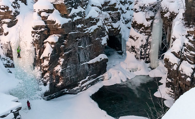 Ice climbers practice on a waterfall in the lower canyon, Abisko, under the glare of an artificial light.
