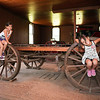 Leilani and Lexi horsing around on a wooden flat wagon.