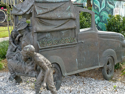 Strawberries play a major role in the economy of Ponchatoula, LA.. Here it is depicted by a bronze rendering of a delivery/sales truck  with the salesman providing samples to some patrons. There is a Strawberry Festival held here each year which draws thousands of visitors.