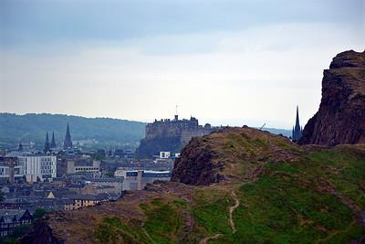 A peak of Edinburgh Castle behind the Salisbury Crags