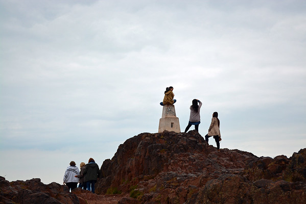 More people standing at - and sitting on - the highest peak marker.