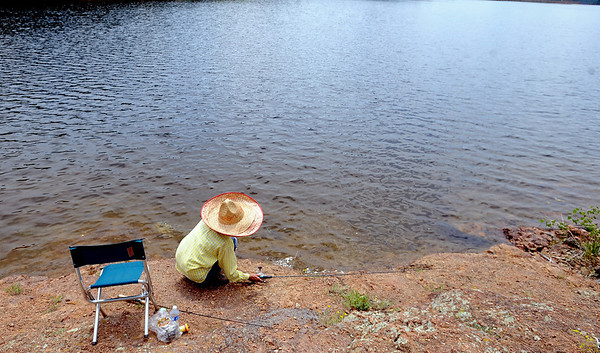 Margie Lin of Denver fishes at Gross Reservoir with her sombrero to block the sun.<br /> A handfull of fishermen had a quiet day at Gross Reservoir on Wednesday.<br /> Cliff Grassmick / July 6, 2011