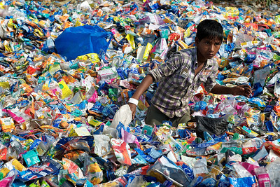 Boy looking for bigger plastic pieces in a pile of plastic bottle labels, Dharavi.
