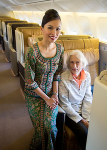 Carol is seated in style by the Singapore Stewardess.