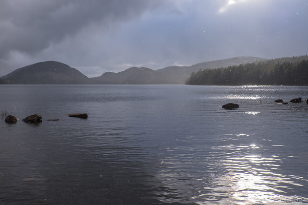 after a snow squall, flurries still float above Eagle Lake in Acadia National Park