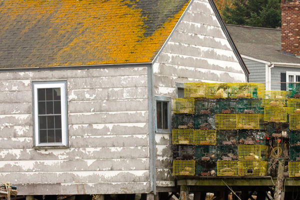 This picture shows a fairly well maintained lobster shack along with all of the stored lobster traps. Most of the lobster trapping is done for the year. Now is the time that most of the fisherman repair their traps and boats. This picture also shows part of a modern home. This seems to imply that some can earn a decent income from this tough business.