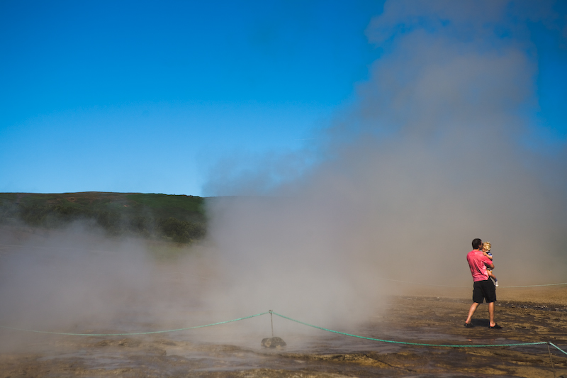 Father holding his child away from the hot steam from Geysir.